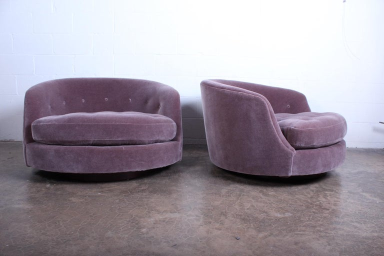 A pair of oversized swivel chairs on walnut bases newly upholstered in Mohair. Designed by Milo Baughman for Thayer Coggin.