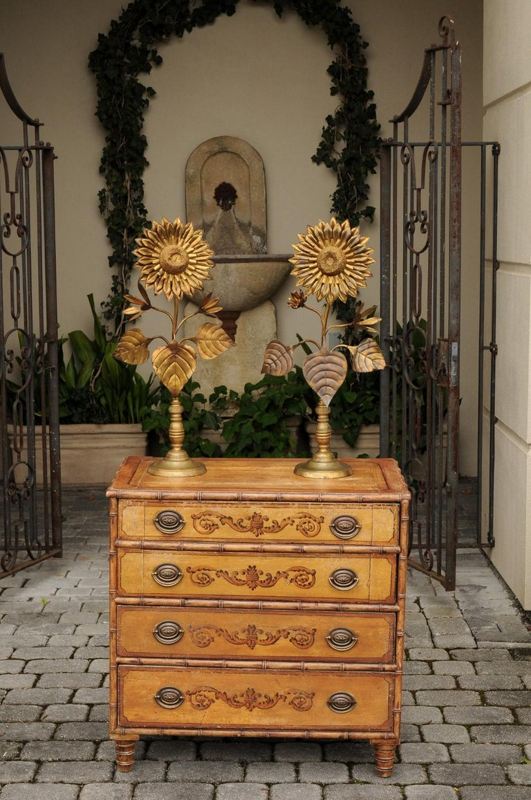 A pair of French vintage brass sunflowers from the mid-20th century, raised on turned-style bases. Born in France during the mid-century period, each of this pair of brass decorative objects features a lovely sunflower, adorned with large leaves and