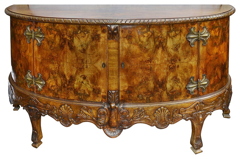 A very impressive and good quality pair of figured Walnut bow fronted Queen Anne style side cabinets, each with wonderful brass hinged and raised on carved cabriole legs with foliate decoration.