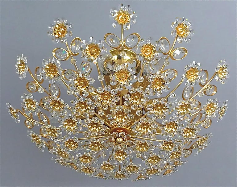 Large round gilt brass metal crystal glass floral flush mount chandelier made by Palwa, Germany, circa 1960-1970, documented in the Palwa sales catalog, labeled with Palwa company decal with model number. The gorgeous ceiling light has lots of