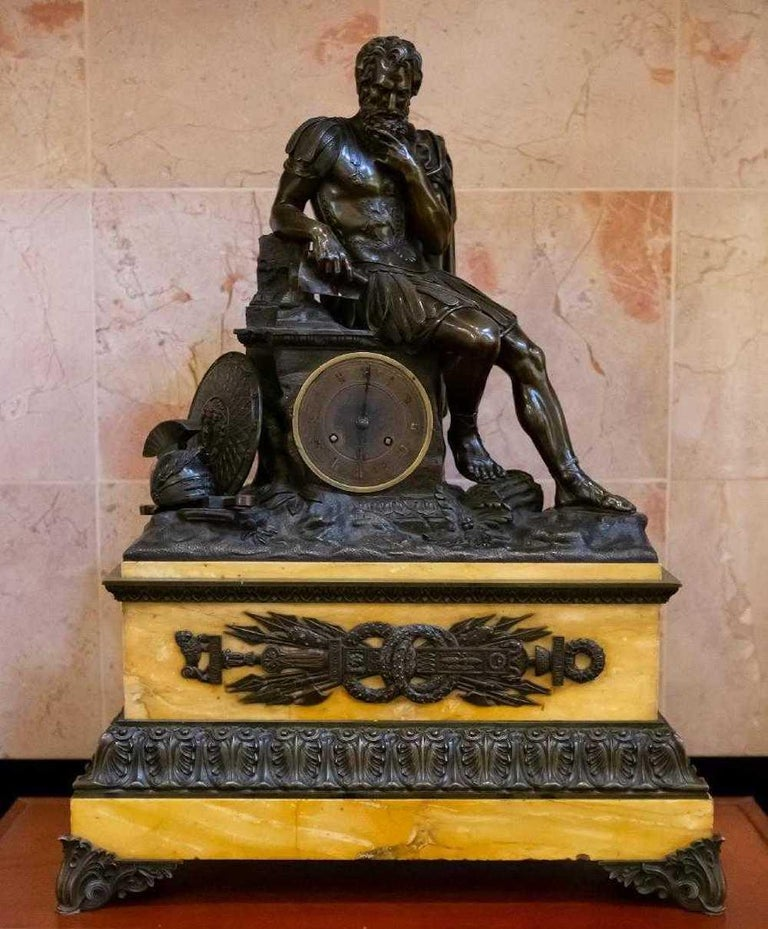 French, 19th century large French patinated bronze and sienna marble figural clock with figure of a seated warrior with helmet and sword holding a scroll inscribed 'Justinien'. Approximate measures: height 28.75