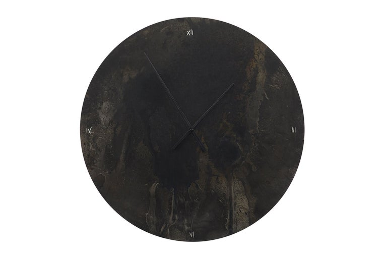 This impressive wall clock is made from steel which is cut and then spot heated with a blowtorch and painted with different black oxides to evoke a warm, vibrating depth to a commonly cold material. The thin gauge steel is then laminated to a