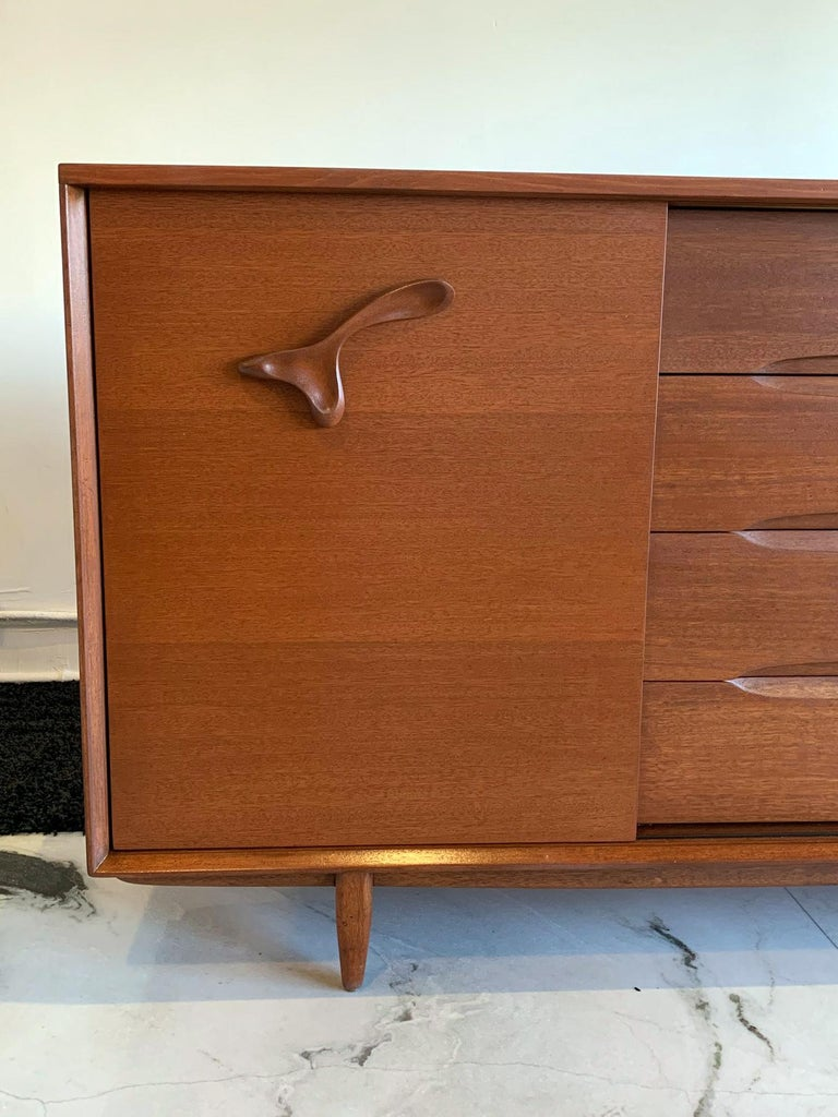 This piece is truly striking! Immediately recognizable by its amoeba style sculpted wooden handles, this John Keal for Brown and Saltman is Mid-Century Modernism at its finest. John Keal Designed in the 1950s for Brown Saltman, this expertly