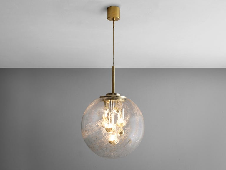 Pendant, in glass and brass, European, 1970s.  Wonderful pendant in brass. This large glass sphere has a fixture with four light-points. In addition of glass decorations inside the sphere, this light creates a stunning light partition. Due the