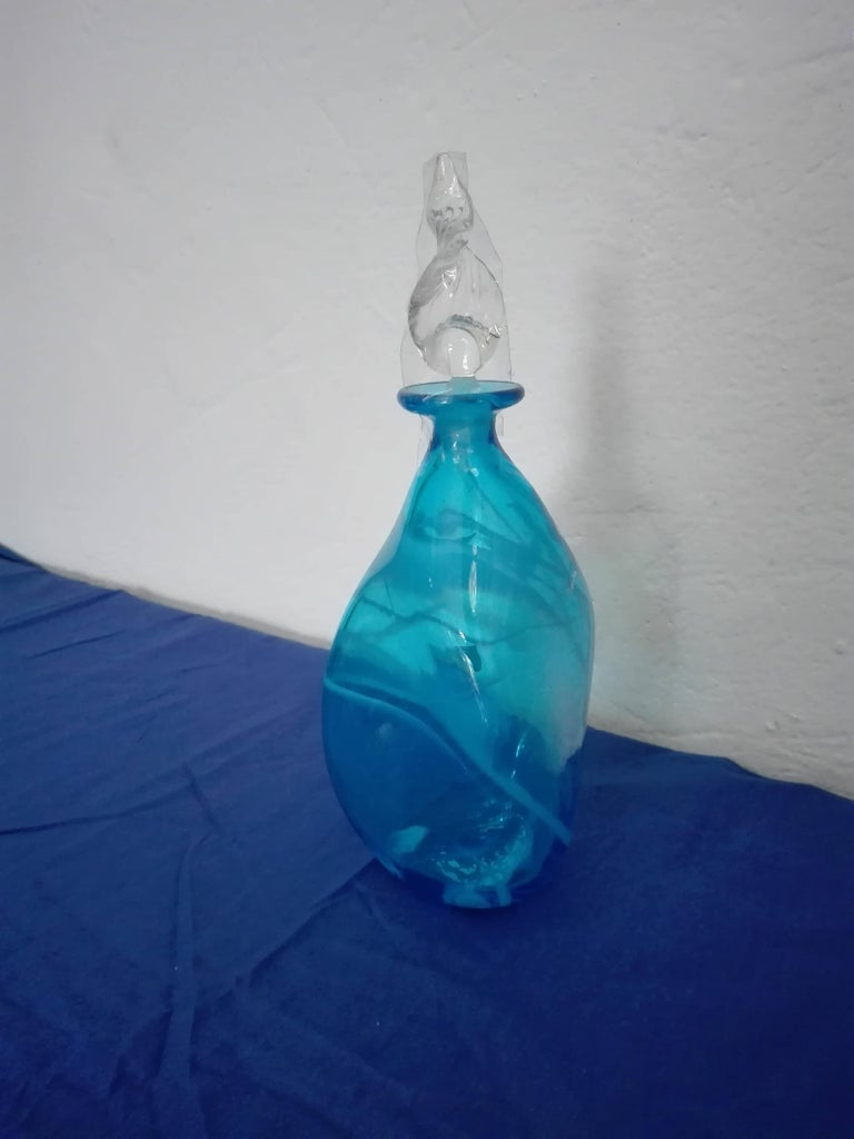 Murano glass bottle of white and light blue color with leaf cap. These magnificent glass objects are entirely handcrafted by our famous Venetian glass masters, who together with his collaborators give light to amazing unique, original and inimitable