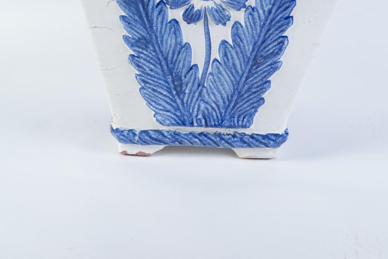 Good size blue and white glazed terra cotta planter from Portugal. Large stylized blue flower on each side. Egg and dart style decoration around the top rim. The base measurement is 9 inches square.