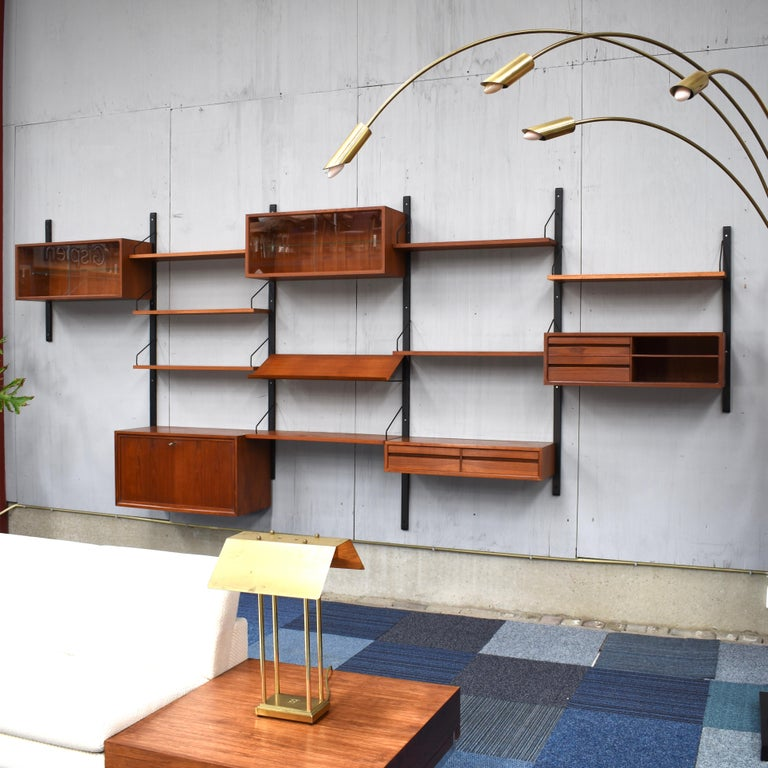 Beautiful Royal series wall unit by Poul Cadovius with much wanted angled lecture shelve. In a beautiful warm wood color and in good condition. This unit features:  – 1 much wanted lecture shelve – 1 fold-down-door cabinet with drawer – 1
