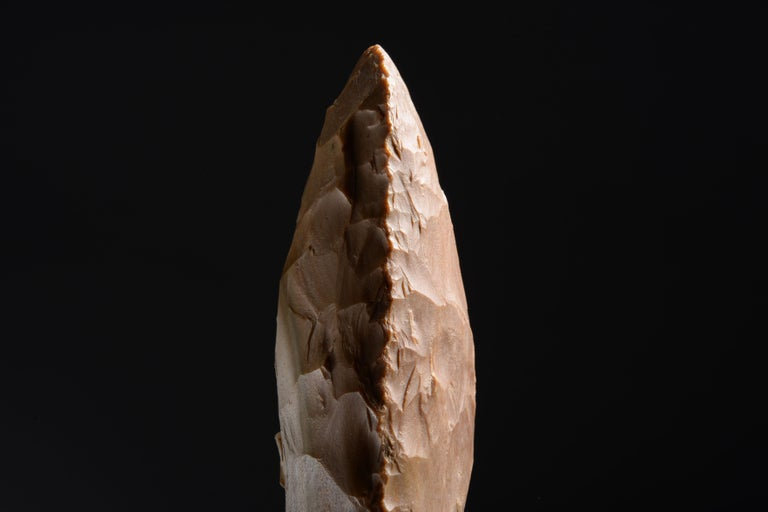 A large, thin-butted Neolithic flint axe found in Mauprévoir, France. Knapped from pink-brown flint, with a white grey streak on one side and with beautiful marks resembling stitching along the edges.  This elegant handaxe was made during the period