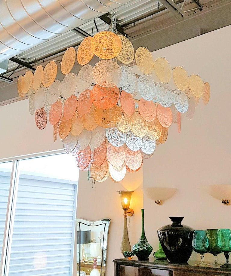 Large Vistosi square and pyramidal Mid-Century Modern chandelier, alternating seven tiers of gold, silver and copper leaf fused metal Murano glass discs. The Murano glass discs are clear with fused gold, silver and copper leaf metal. Very rare