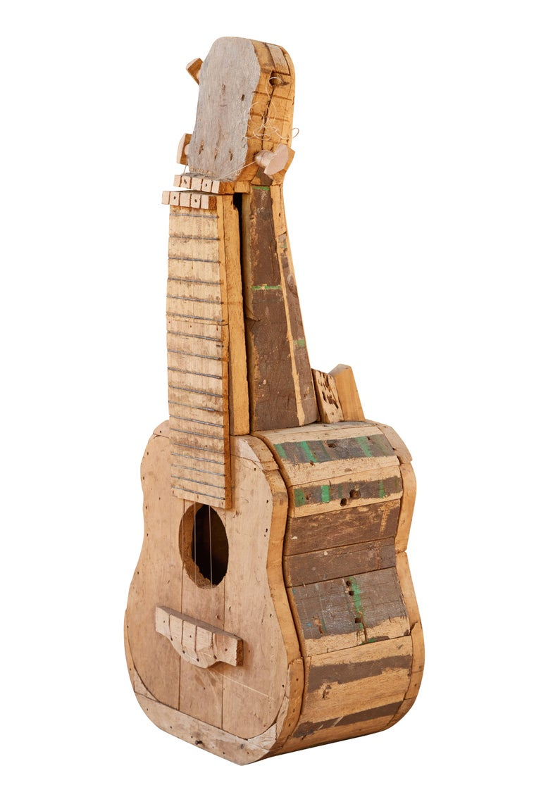 Large reclaimed wood guitar sculpture by African Folk Artist Nii Adum. Handcrafted from recycled woods in Ghana. With the advent of colonization, African carvers began to work European subjects into their repertoires, as well as into their musical