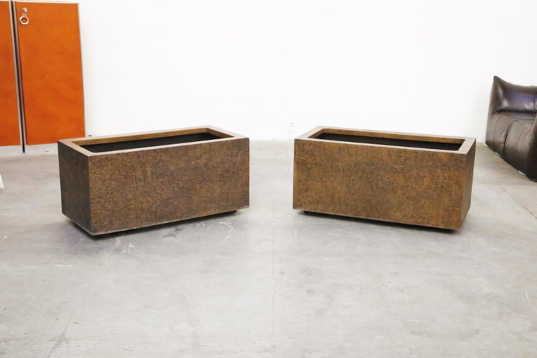 A pair of rare architectural fiberglass planters by Forms and Surfaces designed and produced in the 1970s. These large impressive rectangular pots feature a Brutalist textured bronze colored fiberglass exterior. These large planters are suitable for