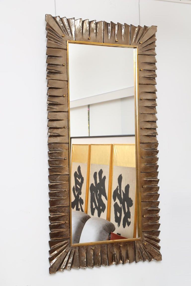 Spectacular pair of amber Murano glass and brass decorative mirrors with solid brass cabochon accents. Glass texture and color are absolutely striking. Pair available. Priced per item. Can be hung vertical or horizontal.