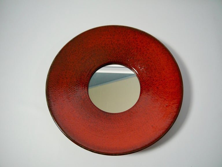 Rare ceramic wall mirror designed by Stig Lindberg for Gustavsberg. Signed with the studio hand and with Gustavsberg sticker. Deep red glazing with black hues.