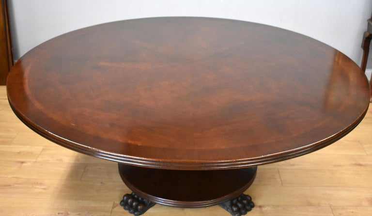 Large Regency style mahogany circular dining table with radial veneers to the top with starburst figured mahogany to the centre. The table stands on a turned column with circular base with large paw feet. Would seat 8 comfortably.
