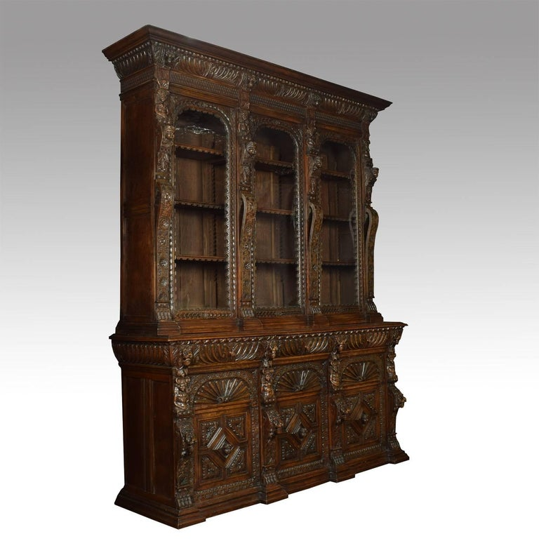 Large Renaissance Revival carved oak three-door bookcase, the deep cornice above a chip-carved and gadrooned frieze above three large glazed doors enclosing adjustable shelved interior, flanked by pilasters carved with lion and figural masks; the