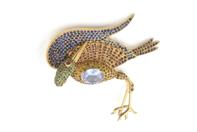 Extraordinary large crane bird brooch accented with blue, green, brown, and golden small rhinestones as well as a large purple crystal as its belly.  The pin is big  3.75