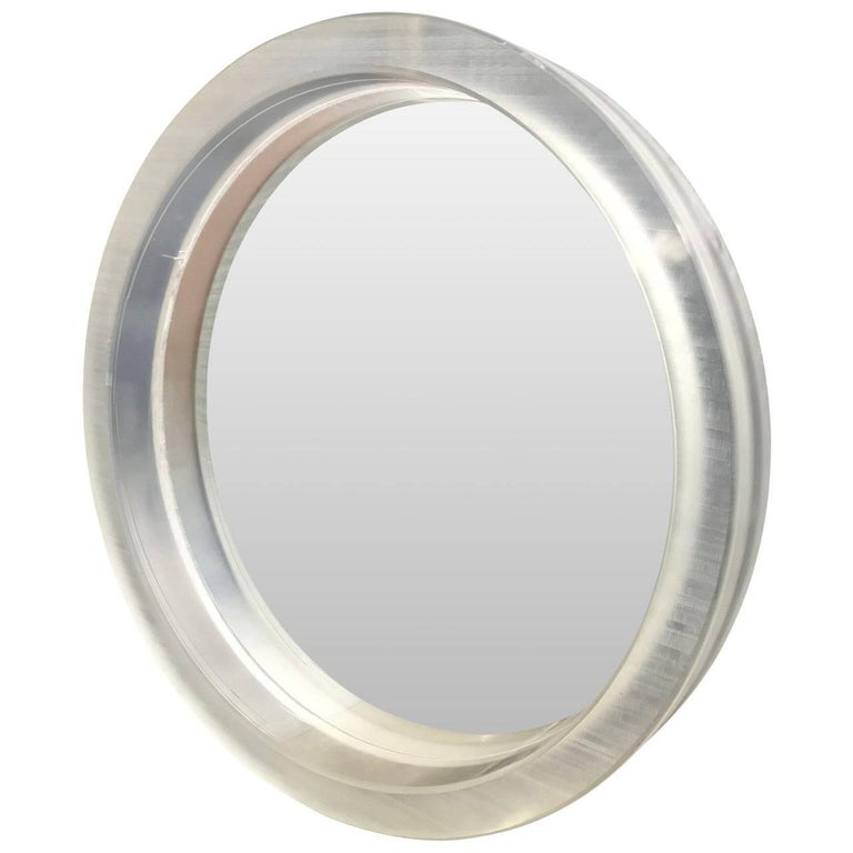 Large round Mid-Century Modern thick Lucite wall mirror  A single thick framed rough cut acrylic or Lucite mirror. The surface on the mirror is rough and individual, due their handcrafted cut. The mirror can be lit from behind in white or a