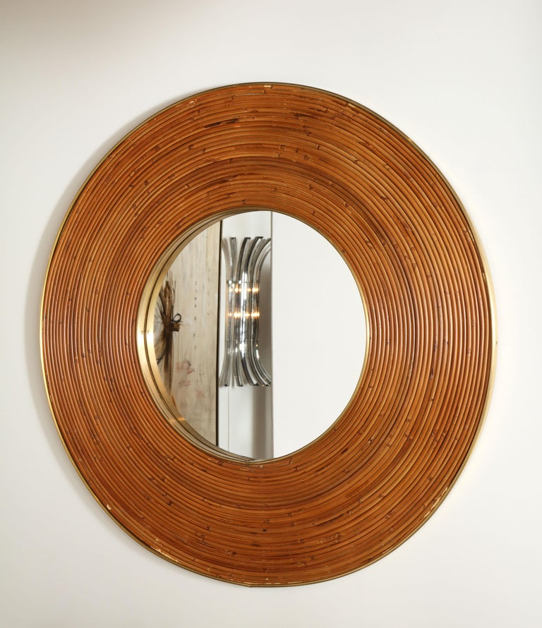 Elegant round mirror consisting of weaved natural reed and polished brass. Excellent  condition. Italy, circa 1970s.