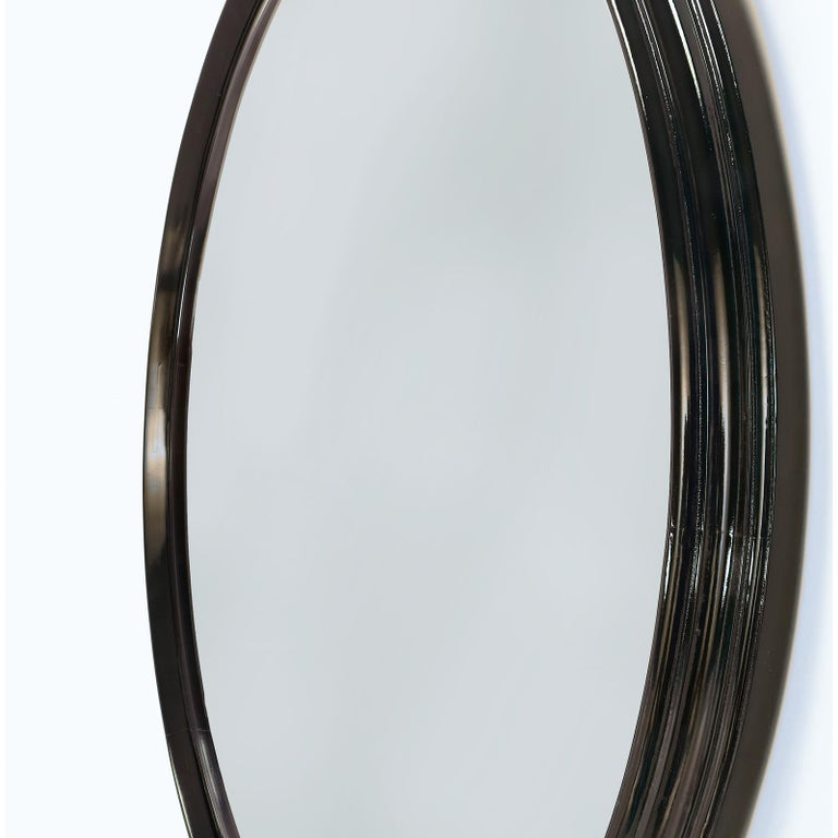 Italy, 1950s Large and elegant round stepped deep brown stained and polished wood mirror with intricate carved ogee molding, beveled glass Dimensions: 42 diameter.