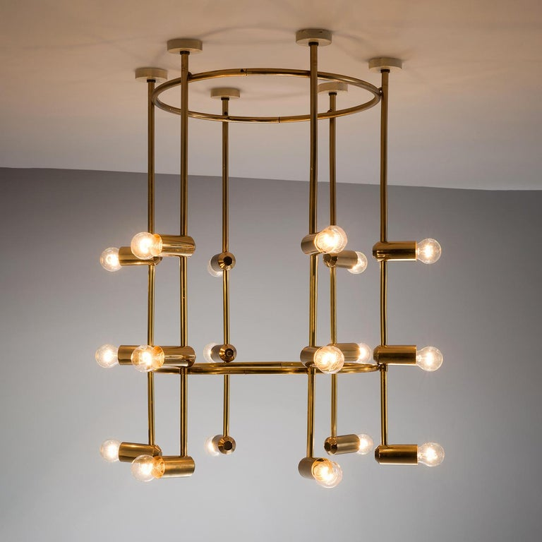 Chandelier, brass, 1960s, Switzerland.  This large yet delicate chandelier is Minimalist yet warm. The light consists of six brass stalks that are attached to a brass ring. There is a lower brass ring on the bottom giving the chandelier both