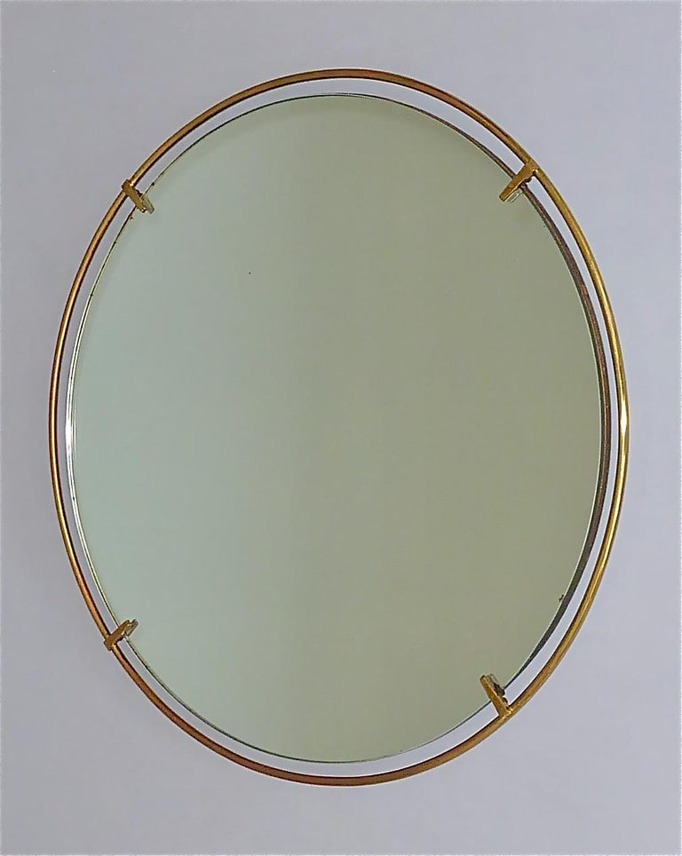 Large round midcentury wall mirror, very in the style of Fontana Arte or Gio Ponti, Italy around 1950. The original mirror glass on a solid wood base has a tubular concentric patinated brass ring which is held by four stylish holder. Simple and
