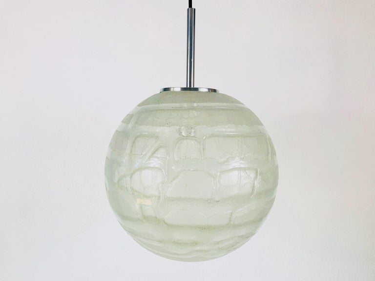 A beautiful glass bowl hanging lamp made in Germany in the 1970s. The light is made of Murano glass. It has an amazing transparent color and it is very solid. The top of the lamp is chrome aluminum.  The light requires one E27 light bulb.
