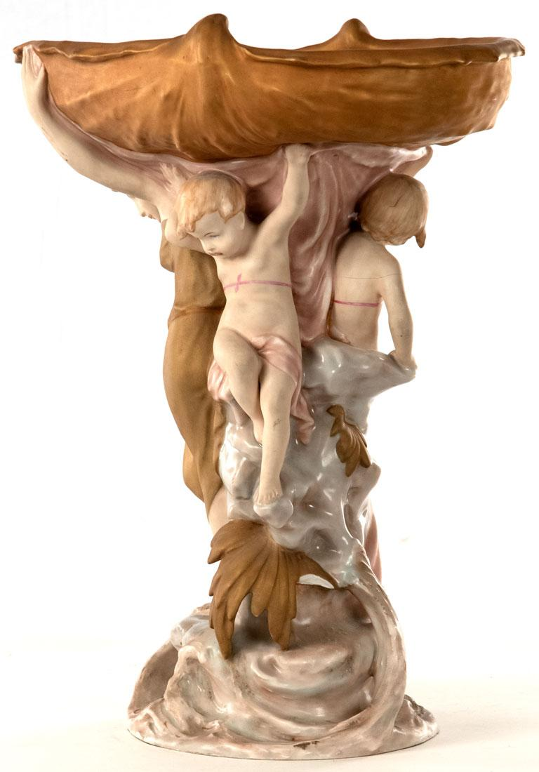 Featuring a nymph an putto frolicking below at the base of a large tree, this porcelain table centerpiece was made by the Czechoslovakian firm.