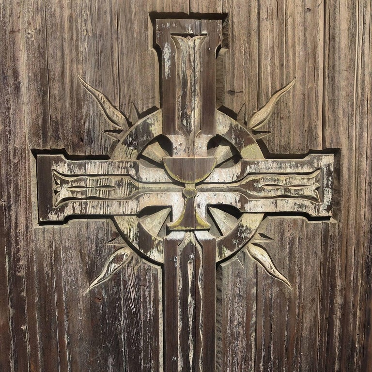 This fantastic free standing wooden panel fits into its' original stepped wooden base, or could be removed and repurposed into a door. The surface is carved with a large crucifix, centered by a chalice cup. The woods display a rustic aged surface