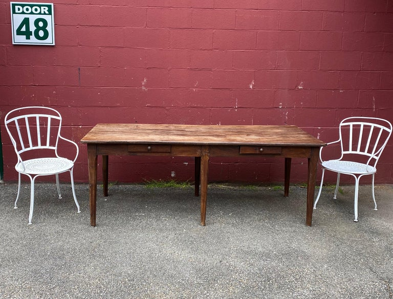 A very large and well made French farm table, possibly in chestnut oak. The top is made up of 3 solid planks and the legs have an interesting tapered fluting detail. There are 2 drawers for storage. The table has been waxed to restore the aged
