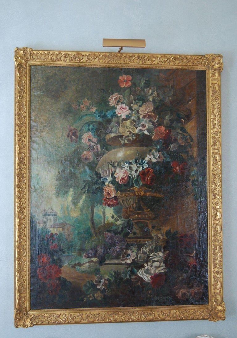 A large painting featuring an exterior marble urn with overflowing flowers set in a garden, likely Dutch and mid-19th century. Very good overall condition in a newer ornate gold leaf frame.