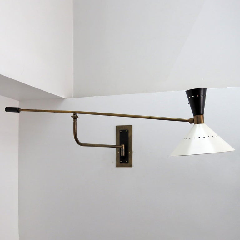 Wonderful Italian swing arm wall light in patinaed brass, with a black and white perforated double cone shade with an on/off switch on the shade and custom solid brass back plate, wired for US standards, one E27 socket & one E12 socket each, max.
