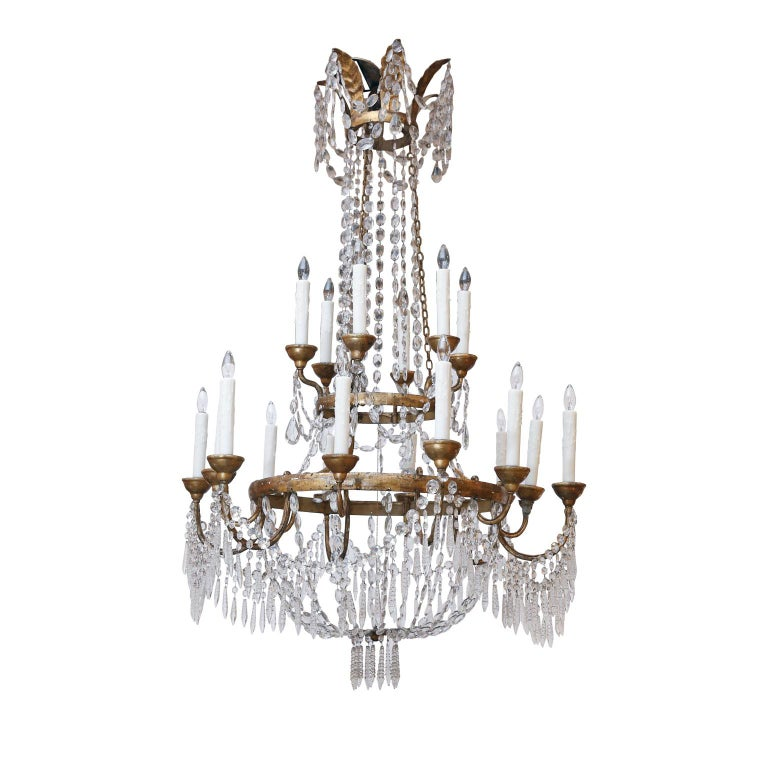 Large-scale neoclassical chandelier from Lucca, Italy. Two gilt-iron ring tiers supporting eighteen arms (twelve lower and six upper). Decorated in original, or early, cut crystal prisms and pressed glass pendants. Newly wired using all UL listed