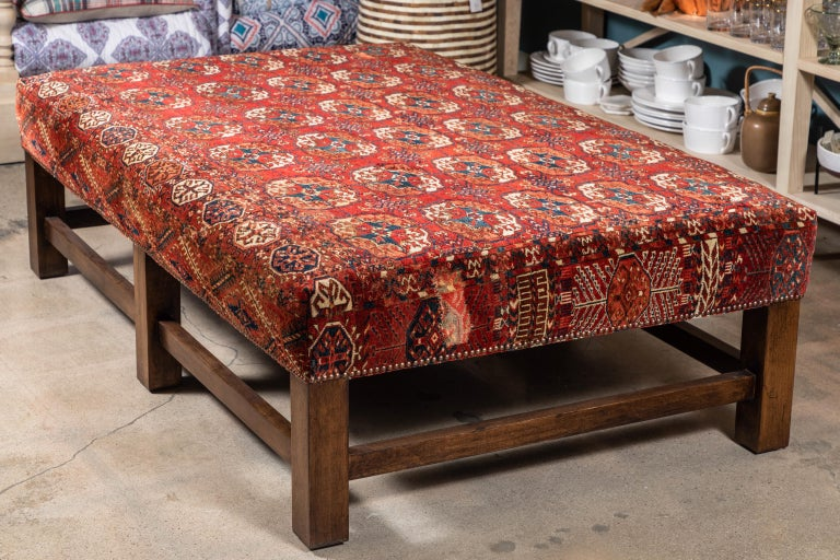 This large scale upholstered ottoman table was custom made to feature a colorful and rich vintage rug with two artfully stitched repairs and evidence of its use. A robust frame on six legs with stretchers is finished in walnut with nailhead details.