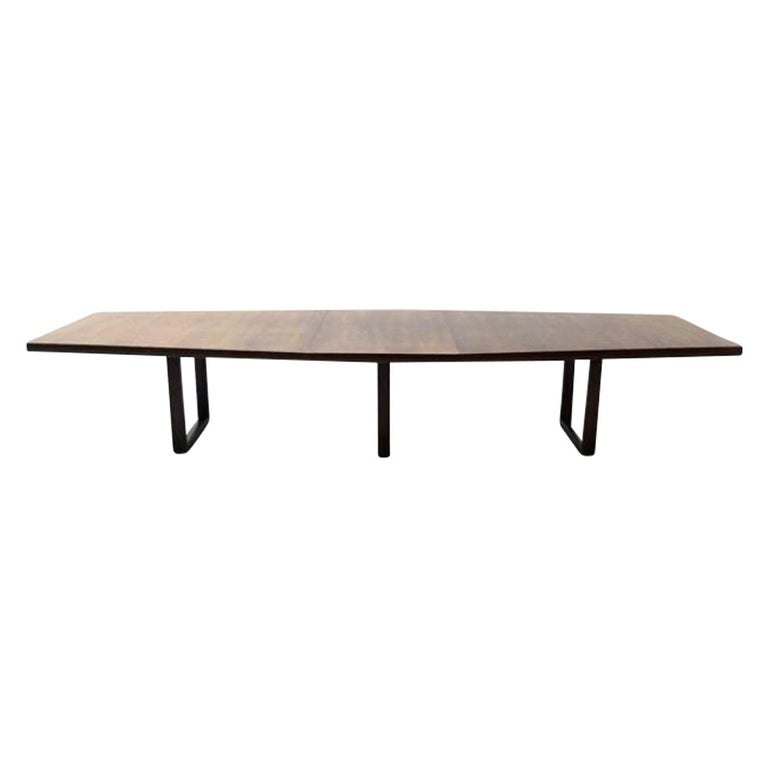 Large midcentury conference or dining table in rosewood veneer. The table has a very cool shape. It is tapered on both ends and wider in the middle. This does not show in all the pictures because of the angle these pictures are taken in. The top