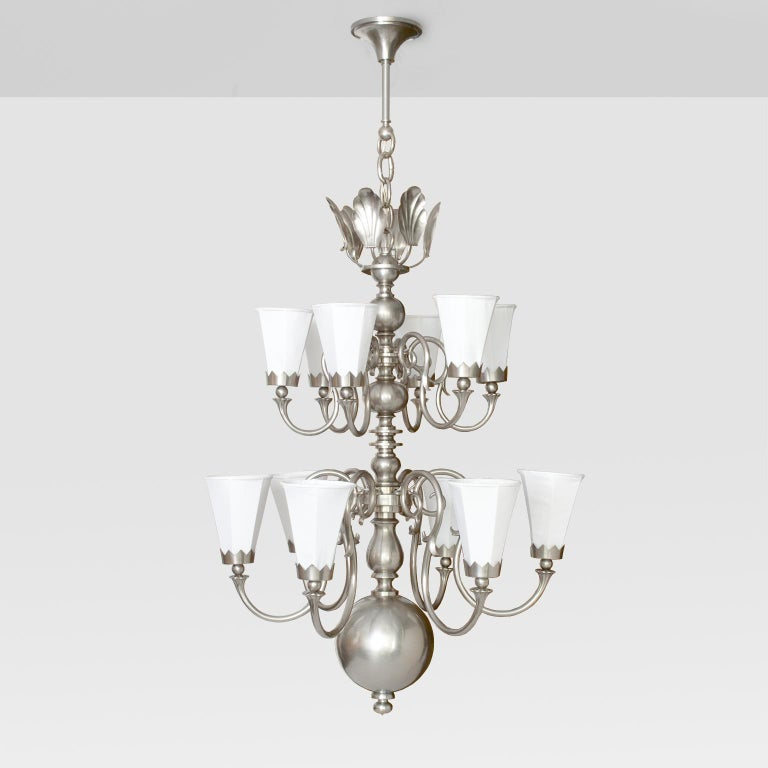 Large 1920's Scandinavian Modern 12-arm chandelier, brass with nickel plate finish. Each arm has a fabric covered 6-sided shade held in place with a crown shaped bobeche. The third-tier is a cluster of stylized shells which reflect light when the