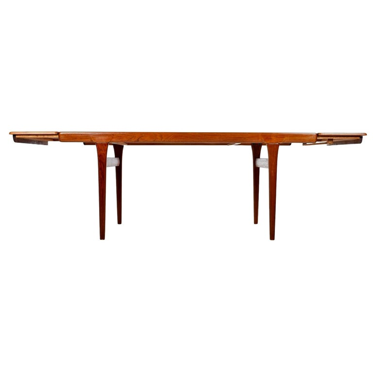 This large dining table stands firm in its solid pine core covered with a teak veneer. This hefty beauty boasts solid teak legs and gorgeous edge banding. The opposing wood grain on the leafs enhance the simple and Minimalist nature of this this