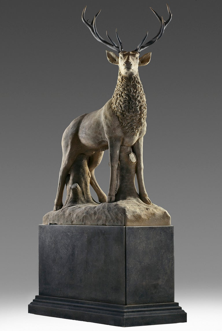 Large sculpted limestone and antler mounted model of a stag / reindeer. Naturalistically modelled standing, above a rectangular section limestone plinth, 325 cm. high overall, the base 100 cm. high.