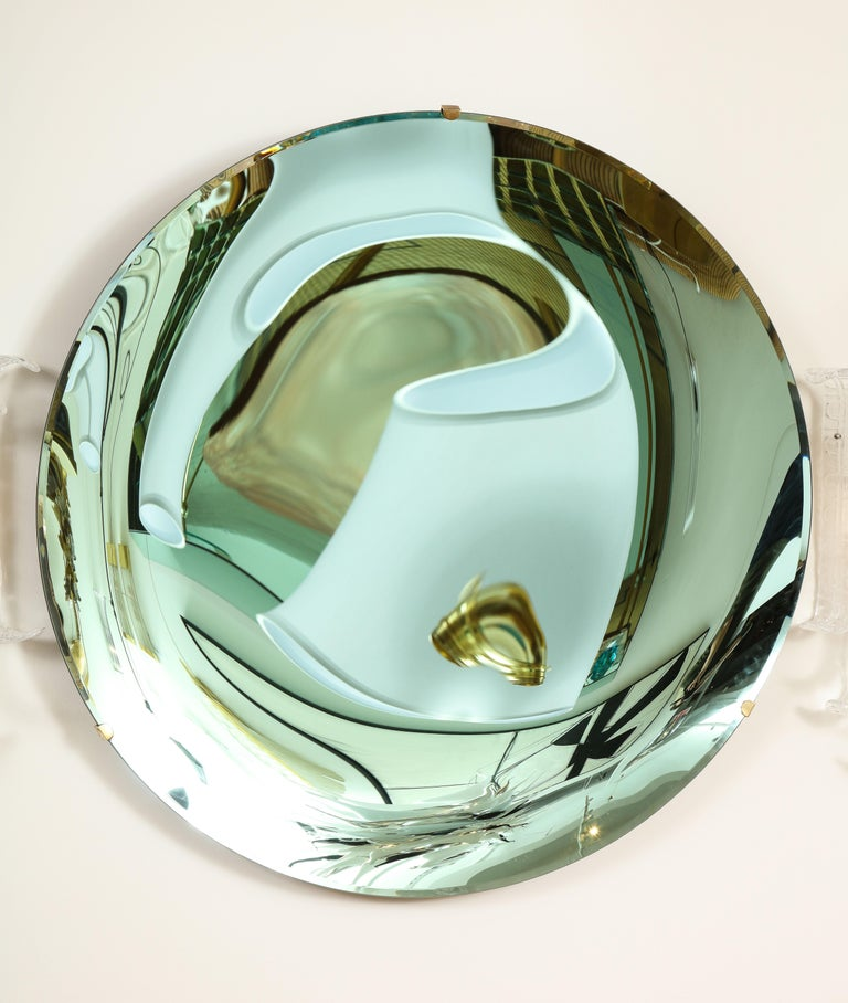 Large round tinted glass in a beautiful soft green hue, thermoformed into a sculptural concave form and mirrored. Mounted on a brass structure that is attached to wall. Hand casted in Milan, Italy, 2021.