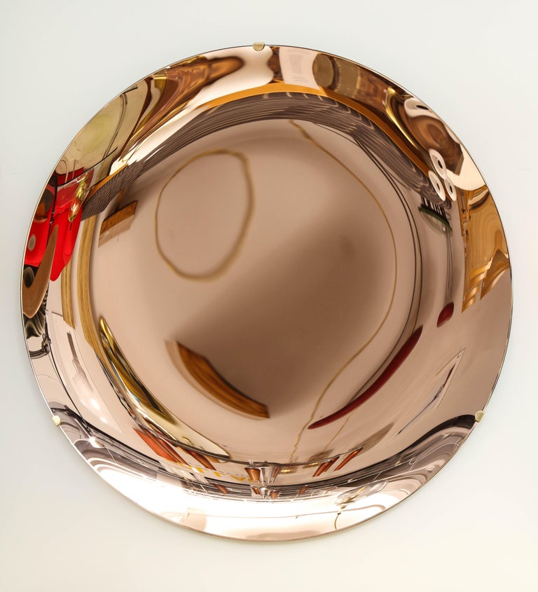 Large Round tinted glass in a beautiful soft salmon or rose hue, thermoformed into a sculptural concave form and mirrored. Mounted on a brass structure that is attached to wall. Hand-casted in Milan, Italy, 2021. This mirror is on display at the