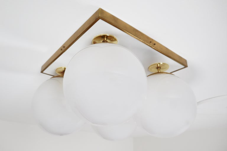 Large set of midcentury ceiling brass ceiling lights, chandeliers, flush mounts by designer and manufacturer Preciosa and produced in Czech Republic the early 1970s. Beautiful work with four pearl white glass globes a brass structure. The light