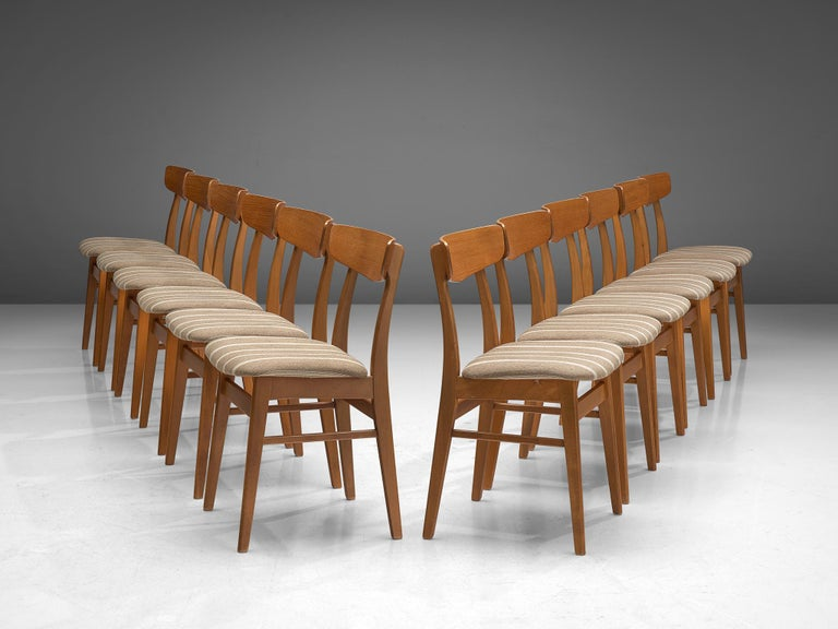 Large set of 12 dining chairs in teak, Denmark, 1960s.  These well made Danish dining chairs were crafted by Farstrup Møbler. The friendly appearance and the construction are typical for Danish style furniture in the 1960s, showing resemblance to