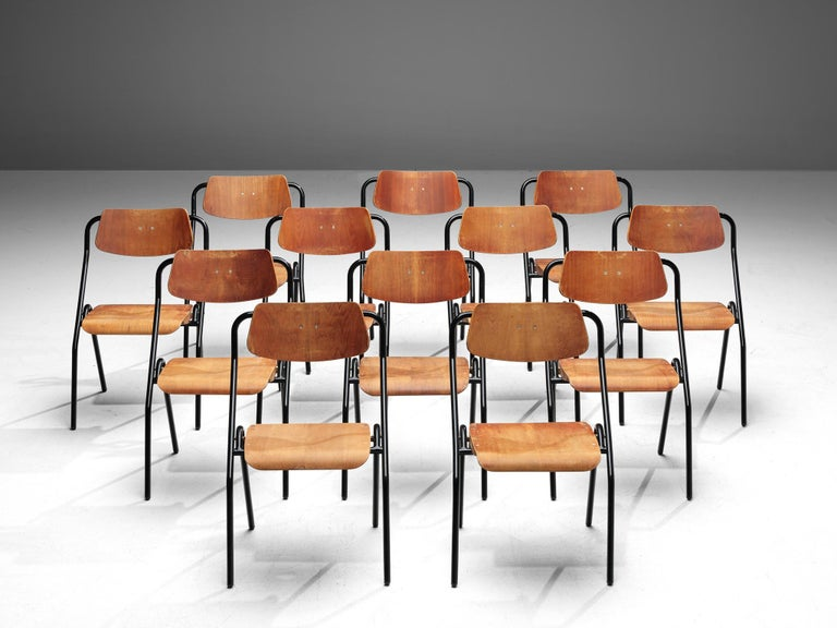Set of 12 chairs, metal and plywood, the Netherlands, circa 1930s  This very large set of midcentury Dutch School chairs would be a great choice for your project if you are looking for chairs that are easy to store. The seats are foldable and the