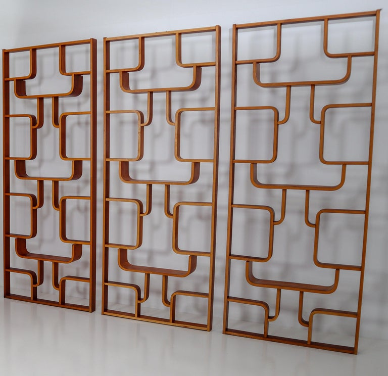 A large set of room dividers from a hotel from Prague purchased from the original owners. These objects can be used as a wall-mounted shelving unit or room divider. Square edges in mahogany color plywood and features geometric patterns. Designed by
