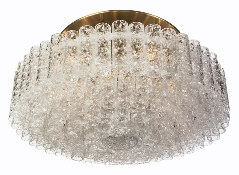 Set of 12 (XL-size) gorgeous, 1950s Mid-Century Modernist flush mount chandeliers was designed by Doria Leuchten, Germany. It features multi-tiered layers of textured ice glass tubes connected to a circular brushed brass frame. The flush mount with