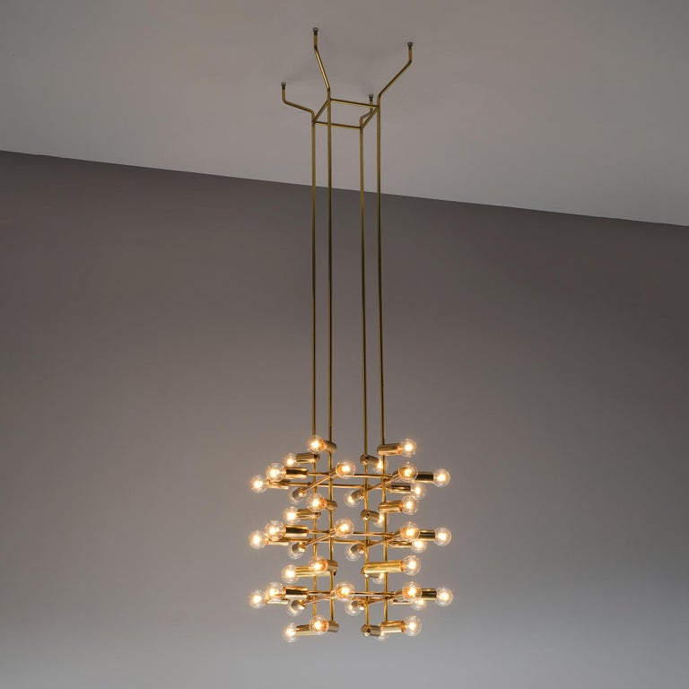 Large set of Swiss chandeliers in brass, Switzerland, 1960s  Each chandelier consists of 40 light bulbs that are placed on the ends of brass horizontal beam. The beams form a cross-like pattern that is attached to the ceiling with long brass stems.