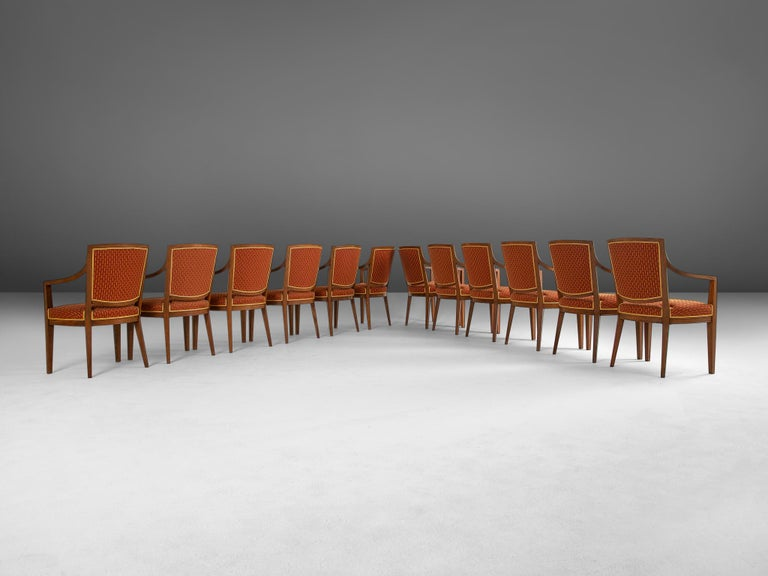 Set of 12 dining room chairs, in oak and fabric, Europe, 1940s.   Large set of 12 armchairs in solid oak. The seat is provided with well designed lines, and elegant details in the wood work. Note how the arm and backrest run smoothly in to each