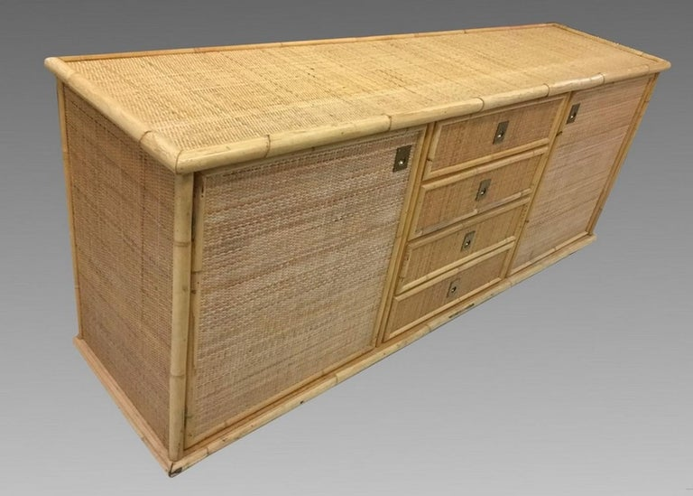 Large sideboard of bamboo and caning on a wooden structure, opening with two doors and four drawers. In excellent original condition.
