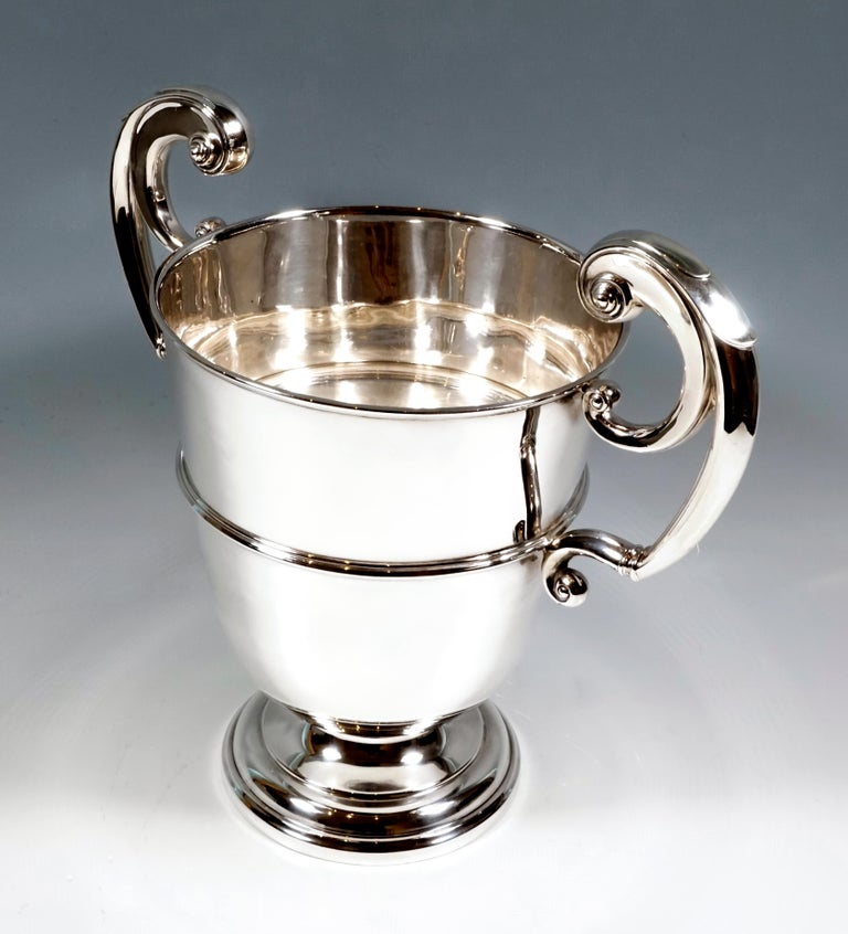 Elegant crater-shaped silver champagne cooler on an offset, stepped, round base with smooth, profiled walls and two large, raised volute-shaped handles.  925 silver  Hallmarks: Master's sign 'WH&SSLD'- William Hutton & Sons Ltd., registered