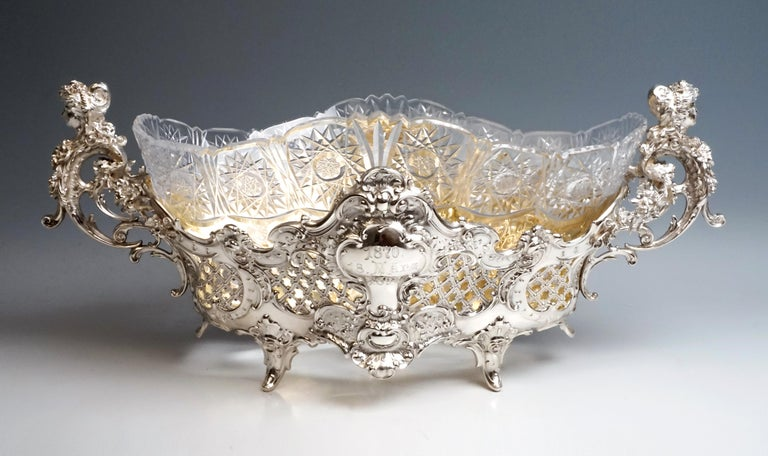 Large silver vessel, widening over a diamond-shaped plan, on the side walls medallions that are elaborately decorated with rocailles, volutes and flower tendrils, in between lattice-like openings with chasing. On the sides, intertwined volutes form