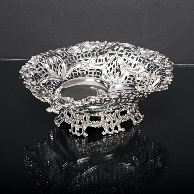 This wonderful and unusually large silver heart-shaped basket has pierced and embossed detail that includes ribbons, scrolls and leaves. It is mounted on a cast heart shape foot to give extra height and impact. This would make a beautiful fruit